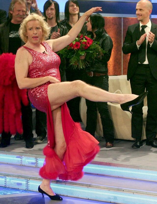 Gottschalk in roter Frauenrobe. Durch den weiten seitlichen Schlitz hebt er das Bein wie eine Cancan-Tänzerin.