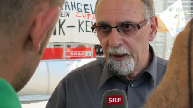 Emmenegger im Interview mit SRF, mit Brille und grauem Hemd.