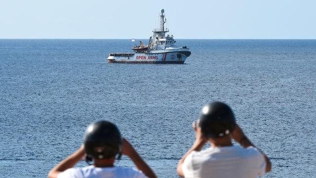 Touristen fotografieren das spanische Rettungsschiff «Open Arms» vor Lampedusa nahe der italienischen Küste.