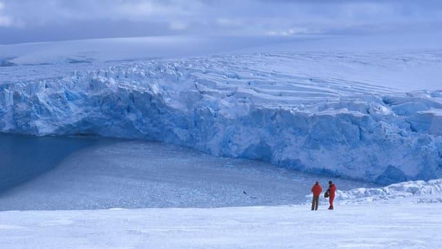 Zwei Menschen am Fusse eines Gletschers.