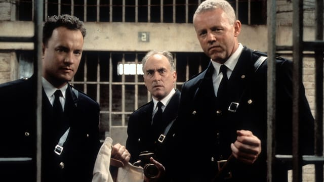 Drei Männer starren in eine Gefängniszelle.