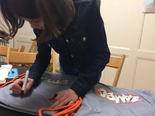 Mädchen unterschreibt auf Rucksack