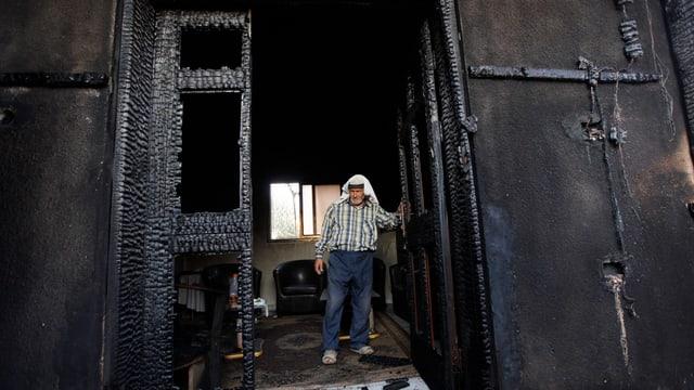 In Palestinais en la ruina da la chasa ch'è arsa suenter l'attatga da fieu ils 31 da fanadur.