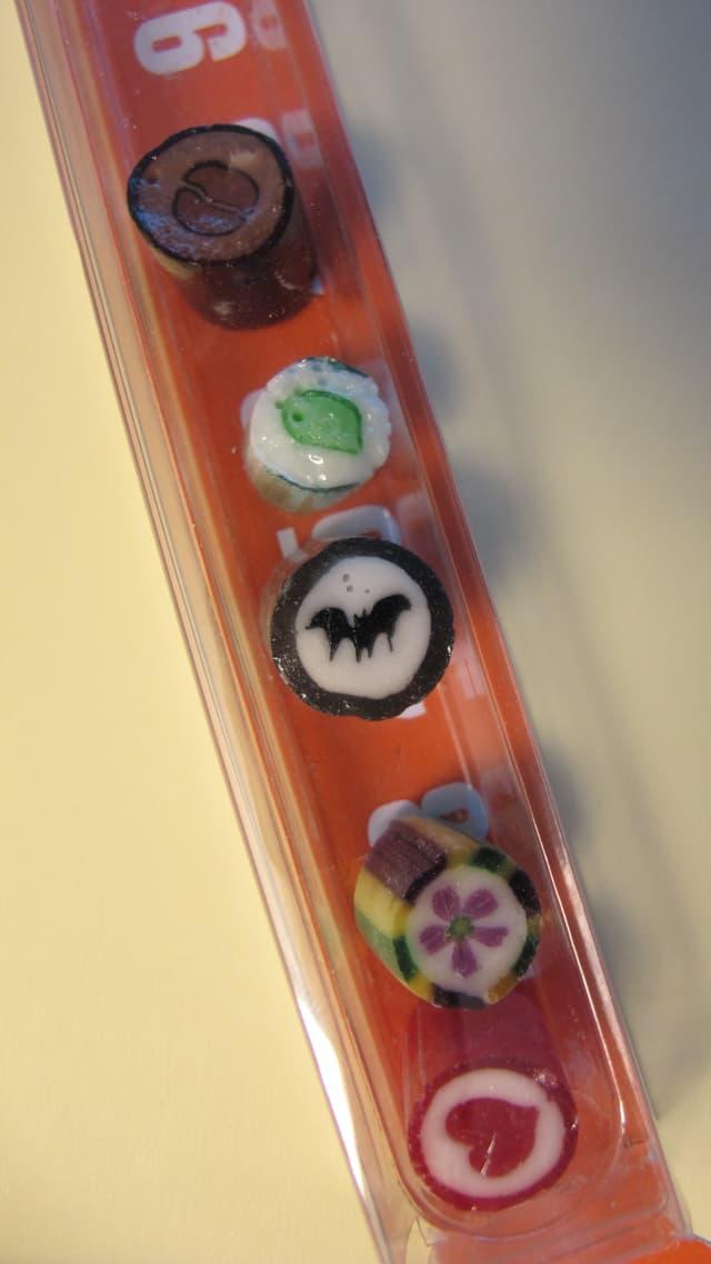 Fünf Bonbons mit Herz, Blume, Fledermaus, Blatt und Kaffee-Motiv.