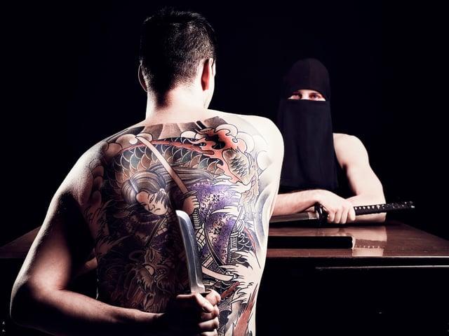 Ein Mann hält ein Messer hinterm Rücken. Vor ihm sitzt ein Maskierter mit Schlagstock.