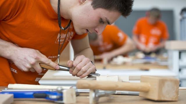 Lehrling bearbeitet an seinem Arbeitsplatz mit einem Werkzeug ein Stück Holz.