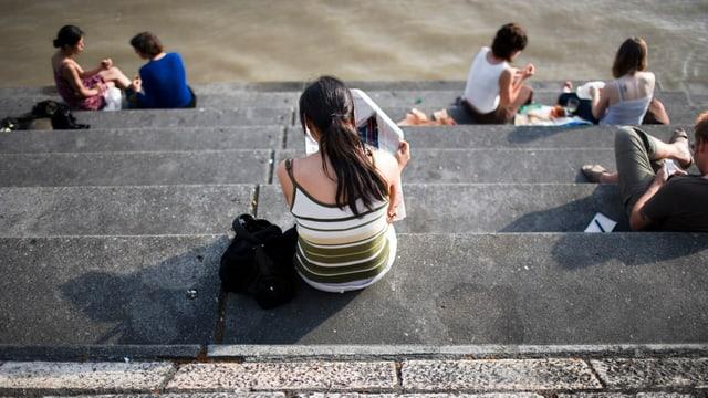 Junge Menschen sitzen auf einer Treppen. Man sieht sie von hinten.