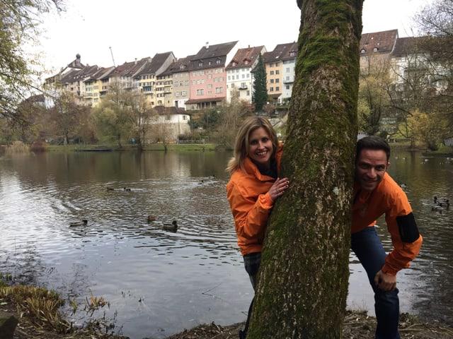 Adrian Küpfer und Sabine Dahinden schauen hinter einehm Baum hervor. Im Hintergrund sieht man eine Stadt.