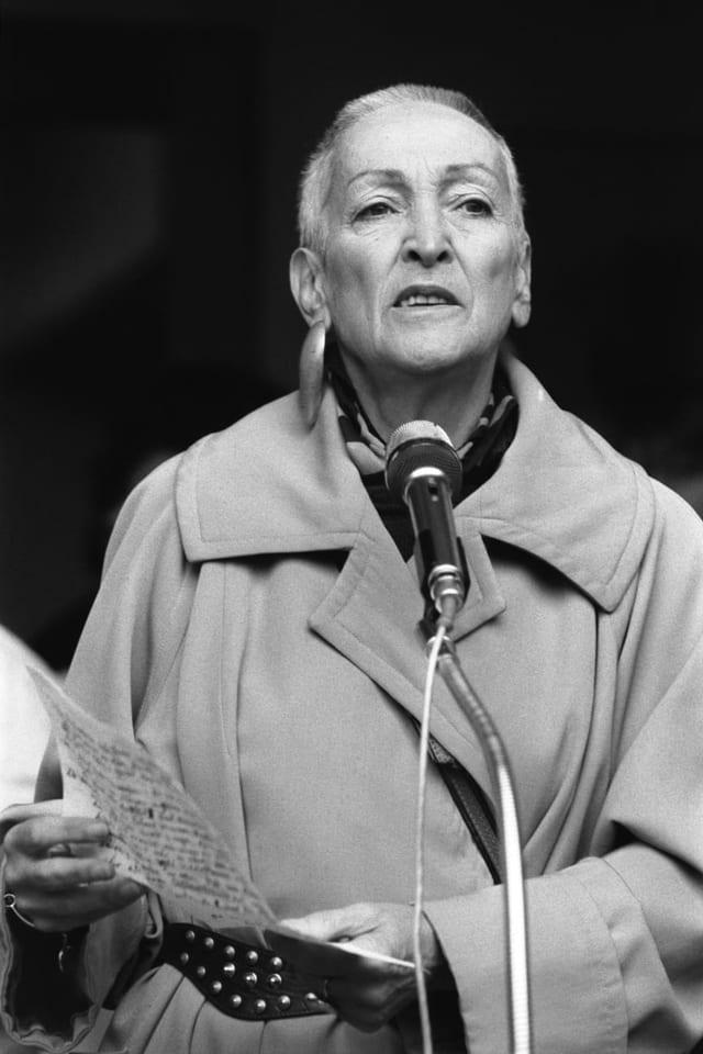 Meret Oppenheim in Trenchcoat vor Mikrofon