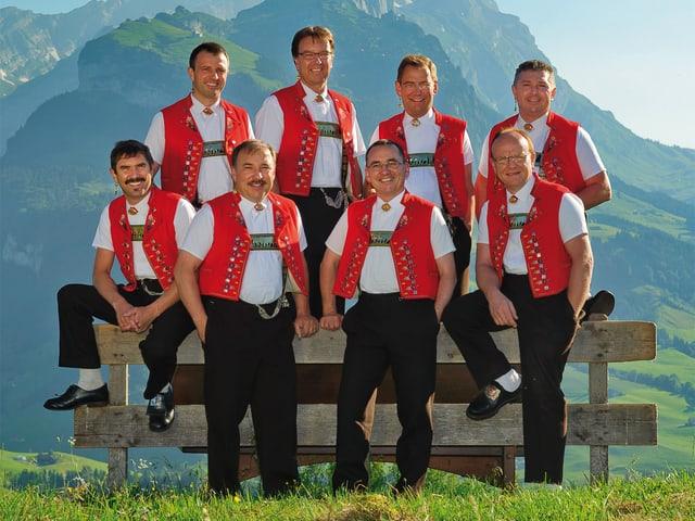 Acht Männer in rot-weissen Appenzeller Trachten vor und hinter einem Holzzaun.