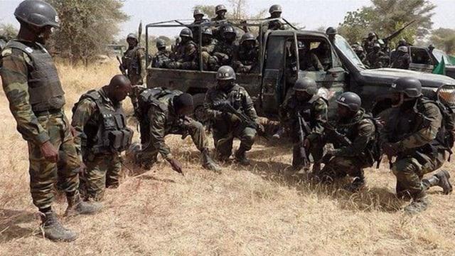 Soldaten vor einem Jeep.