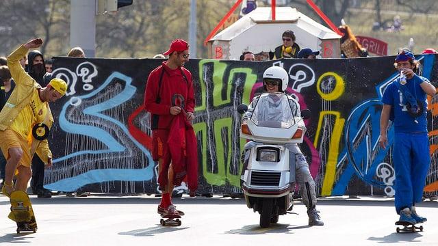 Vier bunt gekleidete Demonstranten rollen auf Skatebords durch die Strasse.