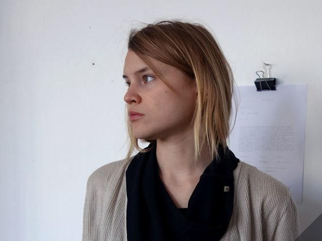 Proträt einer jungen Frau mit langen blonden Haaren. Sie schaut nach rechts.