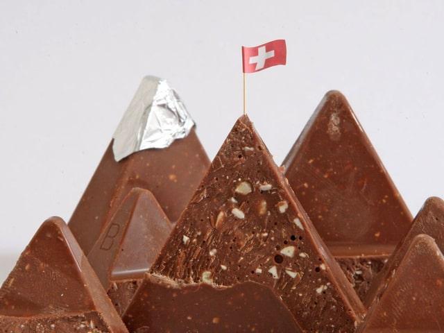 Ein aus Toblerone-Stücken geformtes Gebirge mit Schweizer Flagge auf dem Schokolade-Gipfel.