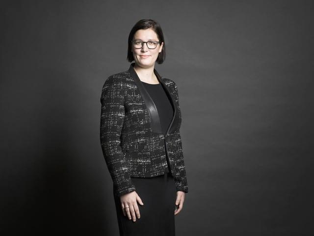 Die Österreicherin Anita Zielina, schwarz gekleidet vor dunklem Hintergrund.