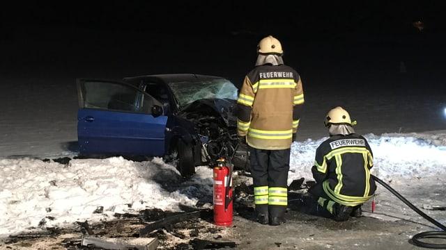 Zwei Feuerwehrmänner stehen, bzw. knien vor dem ausgebrannten Auto