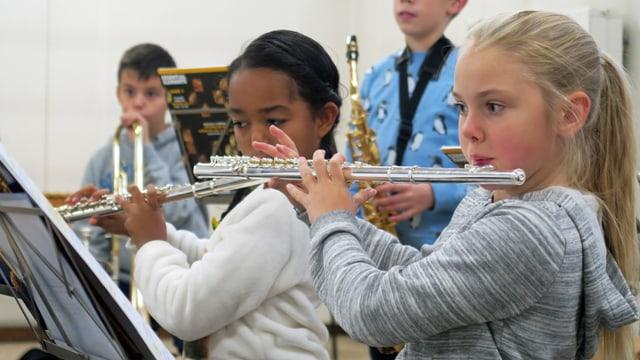 Zwei Mädchen spielen während des Musikunterrichts auf einer Querflöte.