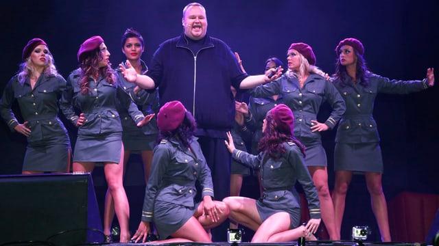 Ein beleibter Mann steht inmitten einer Gruppe von Models in Polizeiuniformen.
