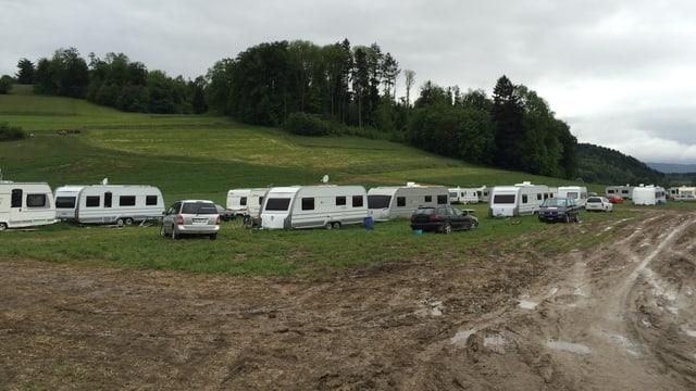 Fuhrpark mit rund 20 Autos und Anhängern von Fahrenden auf einem Feld.