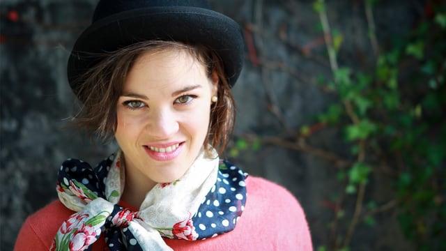 Porträt einer jungen Frau mit Foulard und schwarzem Hut.