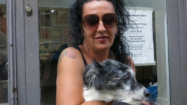 Porträt von Isabel Calvo, auf dem Schoss hat sie einen grau-weissen Hund.