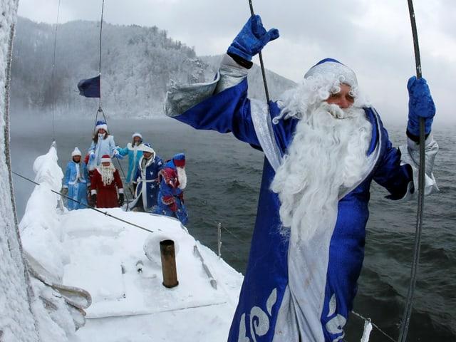 Blau und rote Nikoläuse auf einem Schiff,  überqueren eine Fluss in Sibirien es ist bitter kalt