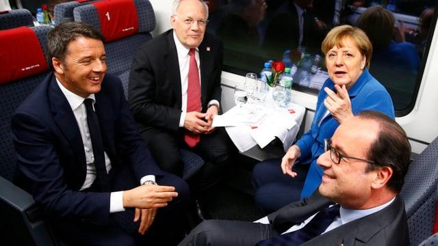 Matteo Renzi, Johann Schneider-Ammann, Angela Merkel und François Hollande sitzen in einem Viererabteil der 1. Klasse, sichtbar gut gelaunt. Angela Merkel zeigt mit dem Finger in Richtung Fotograf.