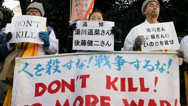 Trauernde japanische Buddhisten halten Schrifttafeln in der Hand.