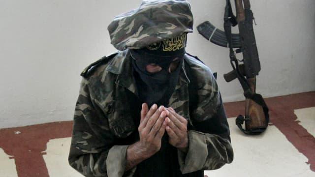 Ein Dschihadist in Uniform und Gesichtsmaske beim Beten, hinter ihm ein Maschinengewehr.