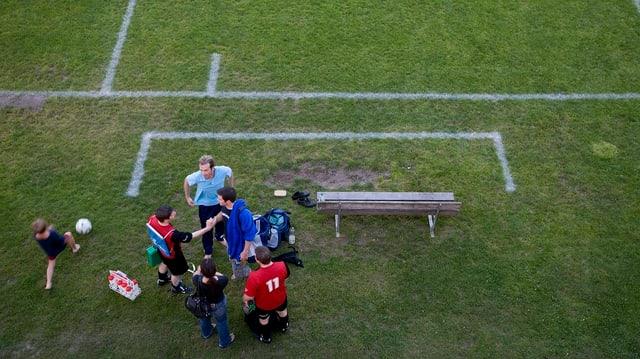 Ein Fussballplatz mit Markierungen und ein paar wenigen Spielern am Rand