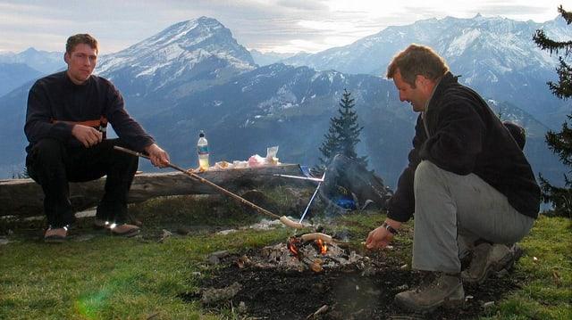 Zwei Männer bräteln Würste über einem Feuer in den Bergen.