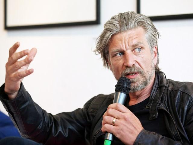 Karl Ove Knausgård hält ein Mikrofon. Er gestikuliert mit einer Hand.