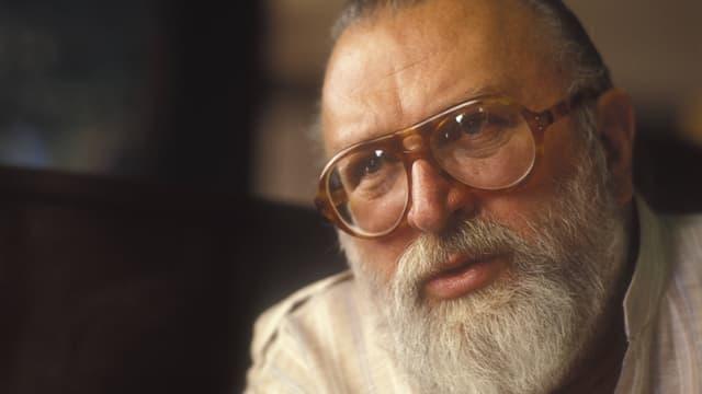 Porträt eines älteren Mannes mit Bart und Brille.