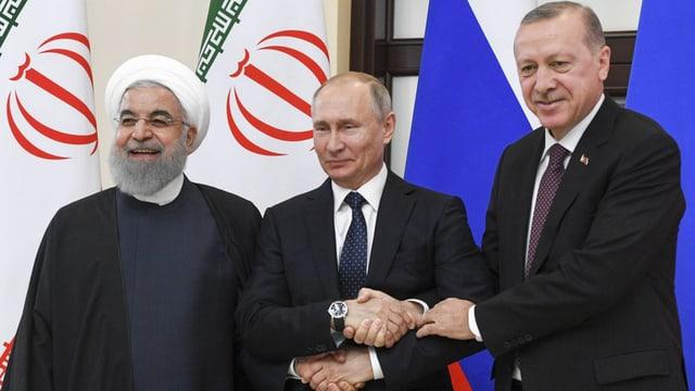 Rohani, Putin und Erdogan geben sich die Hände und lächeln in die Kamera.