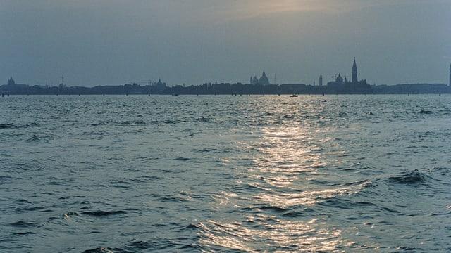 Am Horizont Venedig in Abendstimmung, davor viel Wasser.