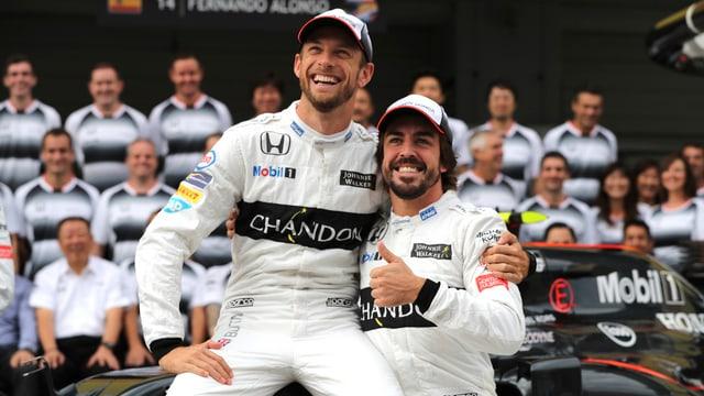 Jenson Button sitzt auf einem Formel-1-Boliden neben Fernando Alonso. Diesem gefällts – der Daumen geht nach oben.