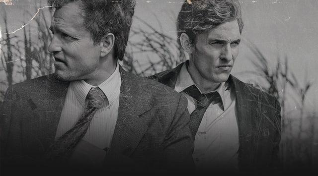 Schwarzweiss Foto, zwei Polizisten stehen nebeneinander und blicken in unterschiedliche Richtungen. Gespielt von den Schauspielern Woody Harrelson und  Matthew McConaughey.