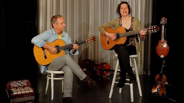 Ein Gitarrist und eine Gitarristin auf der Bühne.