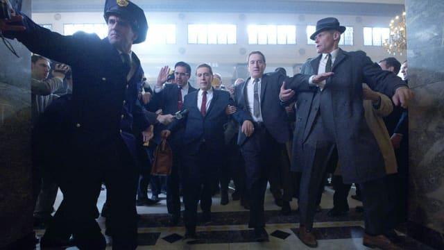 Filmszene: Menschenmenge in einem Gebäude. Ei Polizist macht den Weg frei für einen Mann in Anzug und Krawatte.