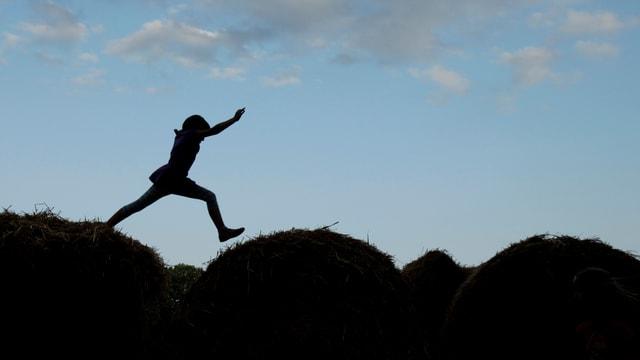 Ein Mädchen springt auf Heuballen herum.