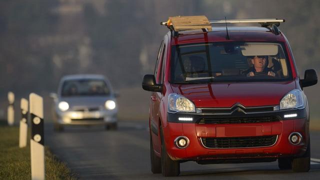 Zwei Autos mit eingeschaltetem Licht fahren auf einer Strasse