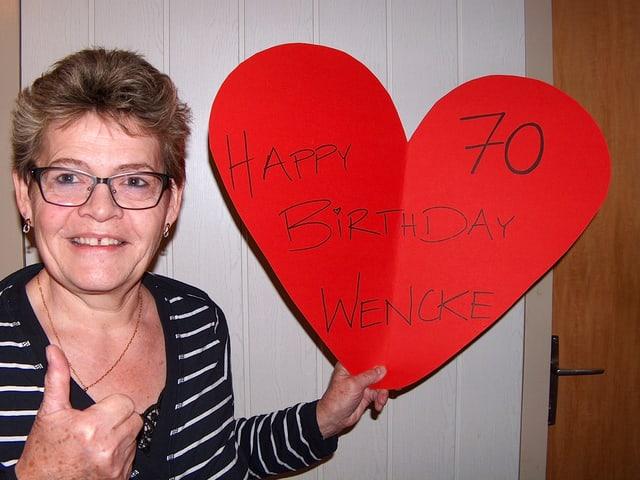 Eine Frau zeigt ein grosses rotes Herz aus Papier.