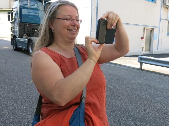 Frau macht Foto mit Handy.