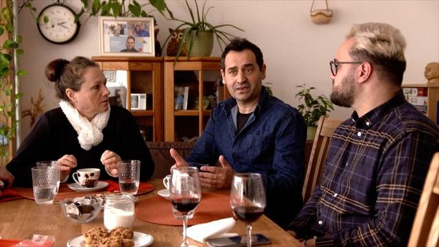 ein älterer Mann und eine Frau sitzen mit ihrem erwachsenen Sohn am Tisch