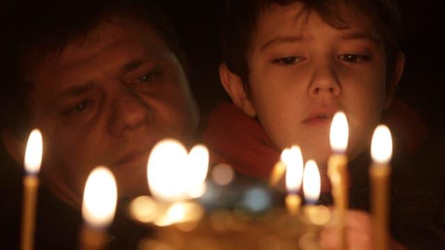 Ein Mann und ein Kind betrachten eine Reihe brennender, dünner Kerzen. Hintergrund dunkel.