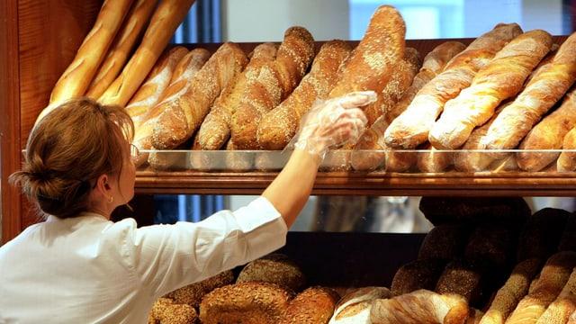 Blick in eine Bäckerei, wo gerade Brote in die Auslage gelegt werden.