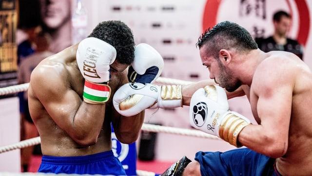 «Carlos» und sein Trainer kämpfen mit Boxhandschuhen im Ring.