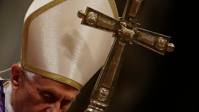 Papst mit einem Kreuz in der Hand, er steht gebückt.