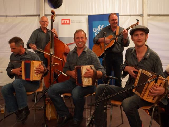Fünf Musikanten mit ihren Instrumenten: drei Schwyzerörgeli, eine Gitarre und ein Kontrabass.