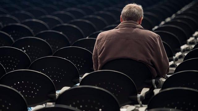 Ein Mann sitzt alleine in einem Saal voller Stühle.